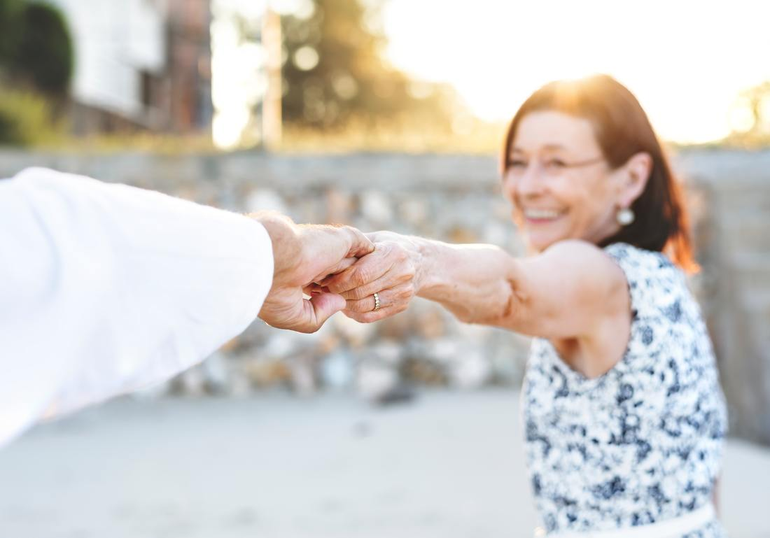 older woman holding hands with man