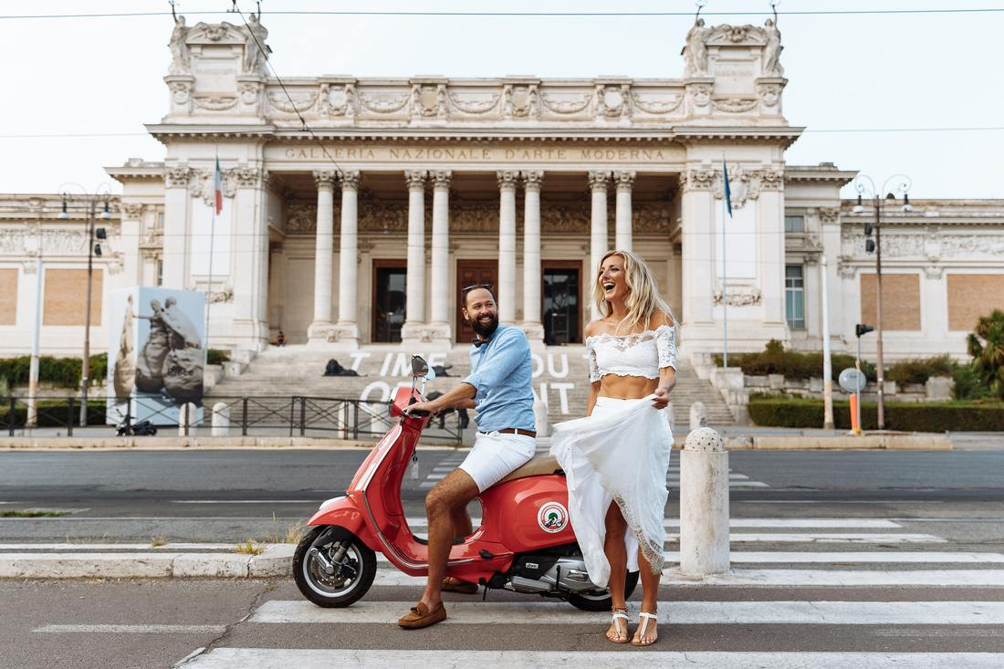 man on red scooter, woman in white
