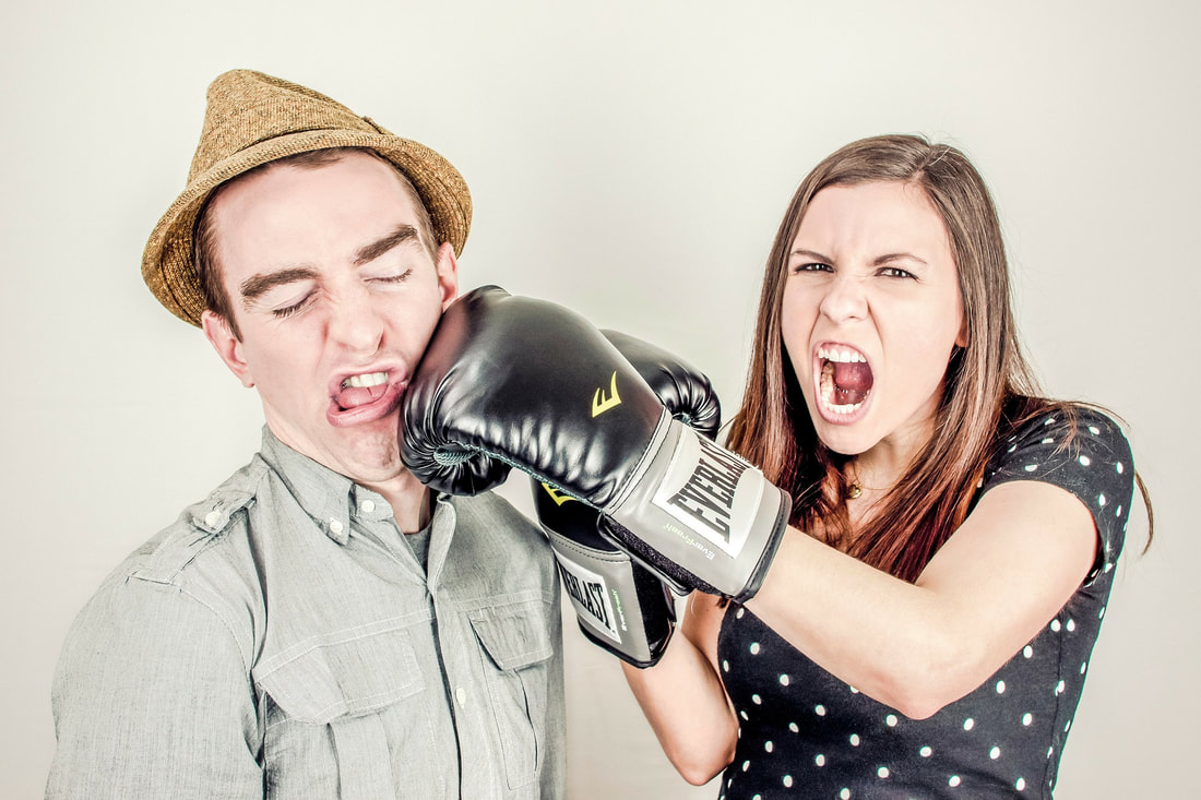 woman wearing boxing gloves punching a man