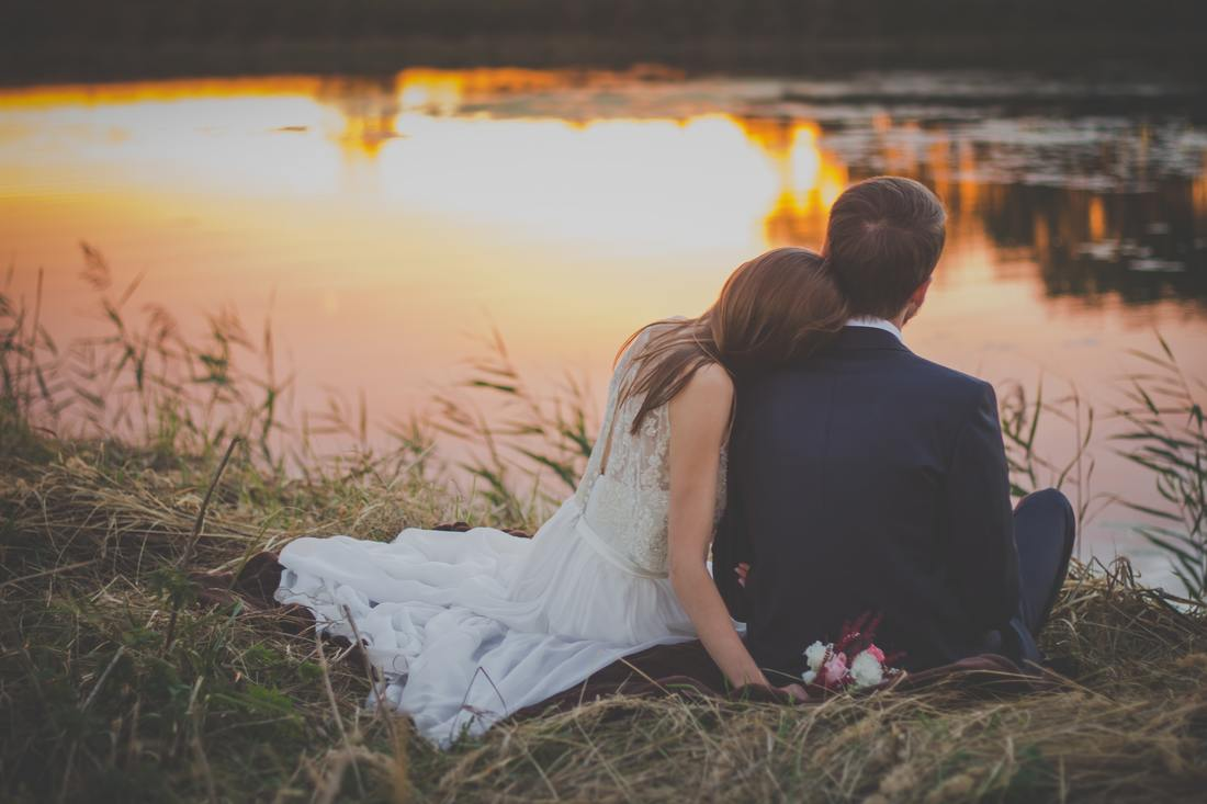 wedding couple sitting on grass by water