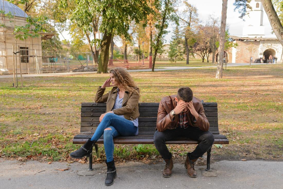 man and woman on a bench looking upset